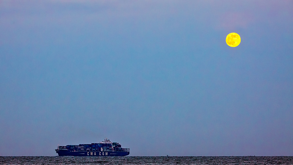 A container ship sails under a full moon to the Georgia Ports Authority Port of Savannah, Saturday, July 9, 2017, in Tybee Island, Ga.  (GPA Photo/Stephen B. Morton)