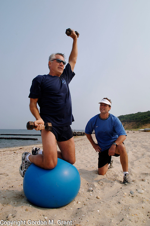 East Hampton, NY - 8/13/05 - Paul Frediani, right, a personal trainer, works with his client Jim Peterson, left, of NYC, on Maidstone Beach in East Hampton, NY August 13, 2005.     (Photo by Gordon M. Grant)<br />