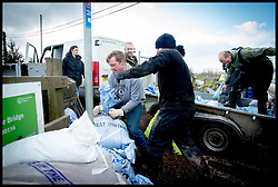 Burrowbridge, Somerset, United Kingdom.Sunday, 9th February 2014. Members of the community pile up sandbags as the  Somerset levels continue to flood.  The levels have been flooded since the start of 2014, with people being forced to leave their homes. Picture by Andrew Parsons / i-Images