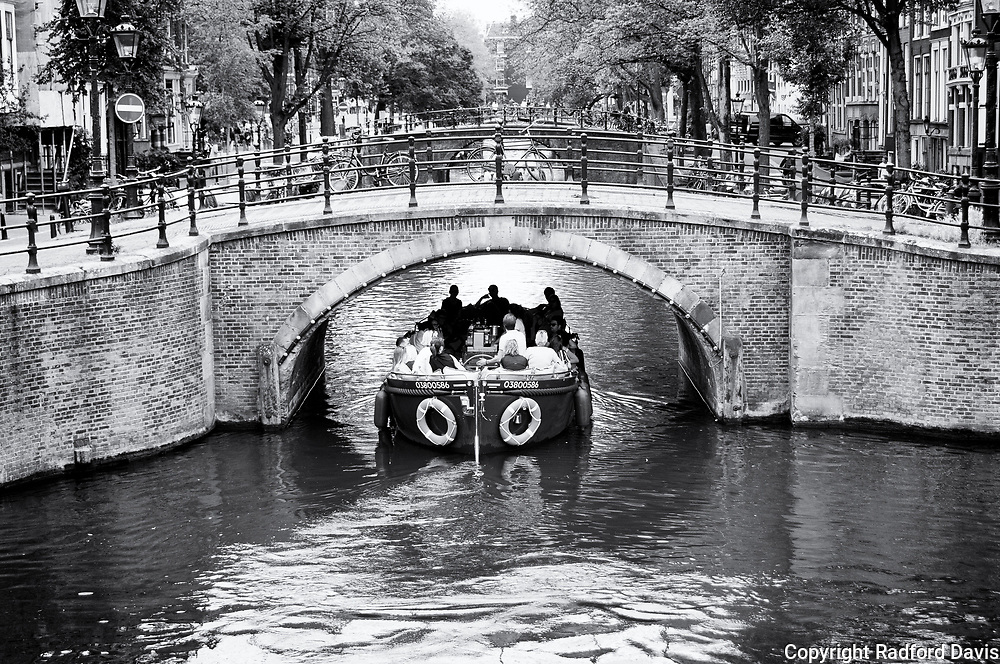 A boat cruises under one of the many bridges of Amsterdam, The Netherlands