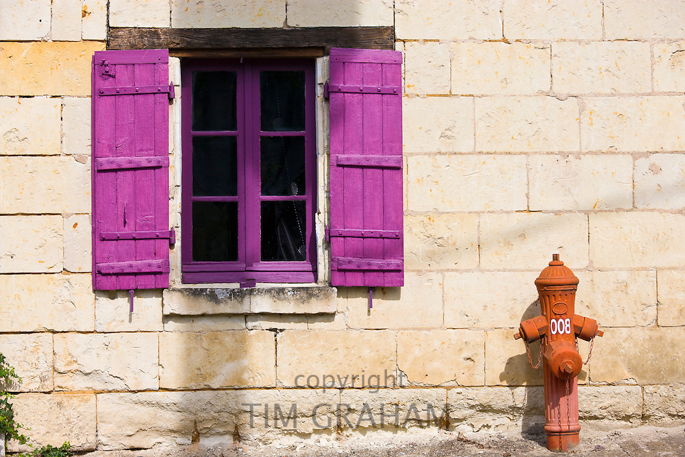 Brightly painted window and traditional water hydrant at Parnay near Saumur in the Loire Valley, France