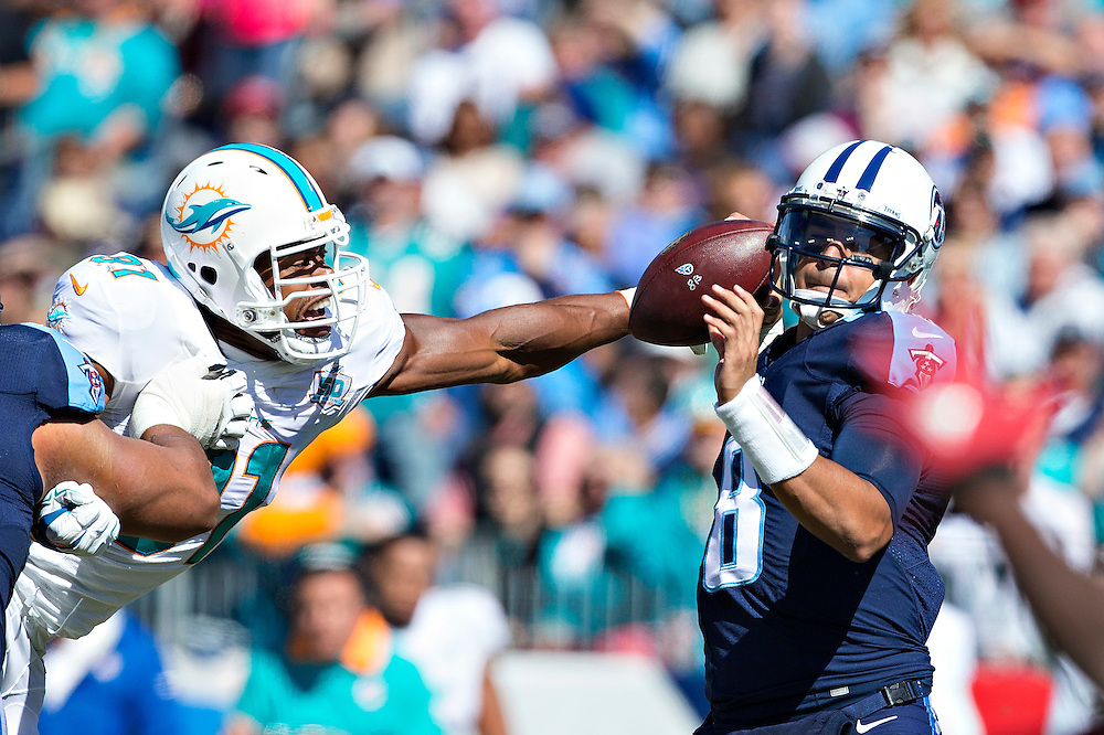 NASHVILLE, TN - OCTOBER 18:  Marcus Mariota #8 of the Tennessee Titans has the ball knocked loose by Cameron Wake #91 of the Miami Dolphins at LP Field on October 18, 2015 in Nashville, Tennessee.  (Photo by Wesley Hitt/Getty Images) *** Local Caption *** Marcus Mariota; Cameron Wake