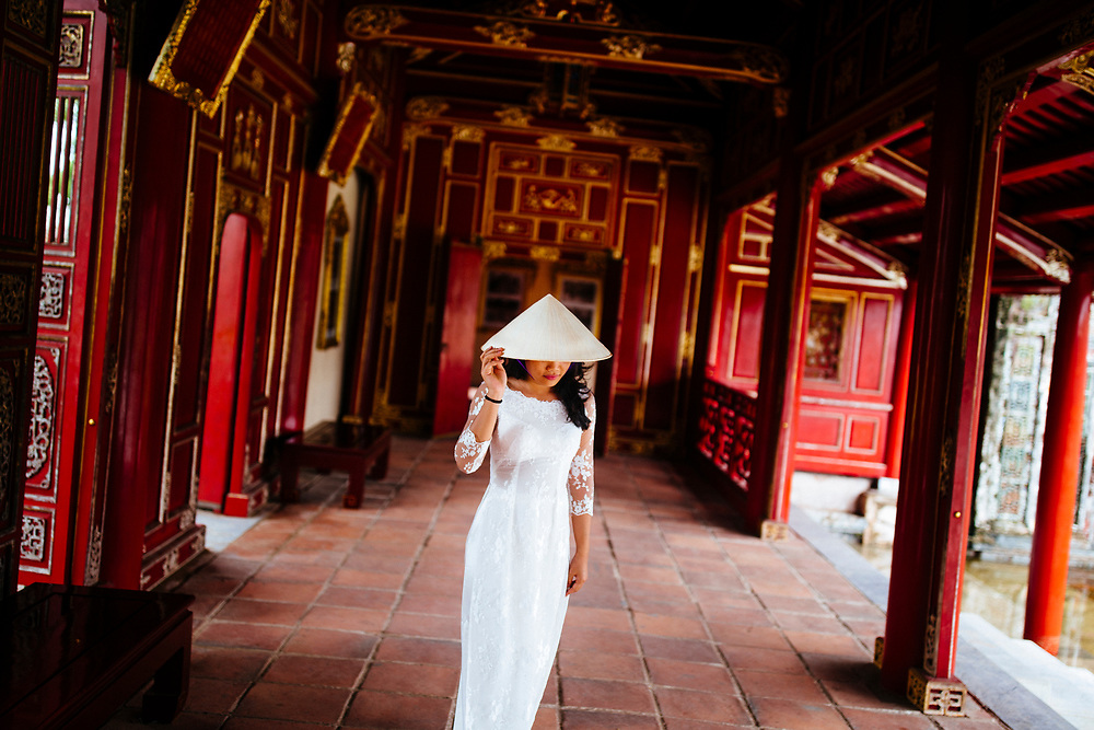 A woman in a white traditional dress at the Imperial Citadel in Hue, Vietnam.
