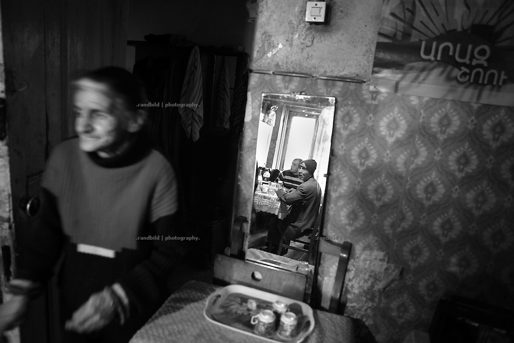 "Rusana enter her living room where she hosts some nighbours for lunch. This image is part of the photoproject ""The Twentieth Spring"", a portrait of caucasian town Shushi 20 years after its so called ""Liberation"" by armenian fighters. In its more than two centuries old history Shushi was ruled by different powers like armeniens, persians, russian or aseris. In 1991 a fierce battle for Karabakhs independence from Azerbaijan began. During the breakdown of Sowjet Union armenians didn´t want to stay within the Republic of Azerbaijan anymore. 1992 armenians manage to takeover ""ancient armenian Shushi"" and pushed out remained aseris forces which had operate a rocket base there. Since then Shushi became an ""armenian town"" again. Today, 20 yeras after statement of Karabakhs independence Shushi tries to find it´s opportunities for it´s future. The less populated town is still affected by devastation and ruins by it´s violent history. Life is mostly a daily struggle for the inhabitants to get expenses covered, caused by a lack of jobs and almost no perspective for a sustainable economic development. Shushi depends on donations by diaspora armenians. On the other hand those donations have made it possible to rebuild a cultural centre, recover new asphalt roads and other infrastructure. 20 years after Shushis fall into armenian hands Babies get born and people won´t never be under aseris rule again. The bloody early 1990´s civil war has moved into the trenches of the frontline 20 kilometer away from Shushi where it stuck since 1994. The karabakh conflict is still not solved and could turn to an open war every day. Nonetheless life goes on on the south caucasian rocky tip above mountainious region of Karabakh where Shushi enthrones ever since centuries."