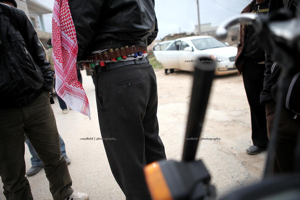 A man wear a belt stuffed with selfmade bullets. Kureen, Province of Idlib, Syria.