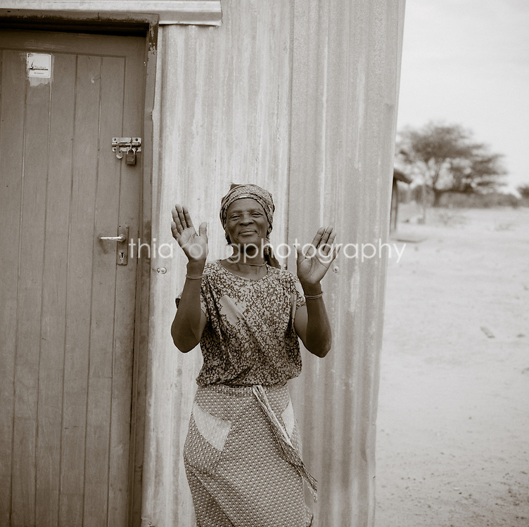 Black and white portrait of warm hearted storekeeper waiving hands with a smile to say the store is closed, even for a jeep full of tourists. Okanvango Delta, Botswana, Africa