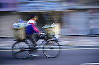 Chinese man riding a bicycle with baskets of food, Kowloon, Hong Kong, China.