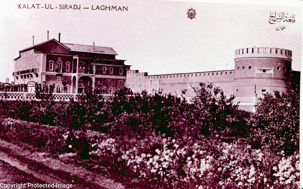 1983<br /> Copy of color post card in Souvenir Afghanistan printed in Paris in 1922, 1924, 1928 Qalat us-Seraj Palace was built by Amir Habibullah ca. 1912-13 at Tigri, now called Mehtarlam, the capital of Laghman Province. The Amir was assassinated on 20 February 1919 while on a hunting trip near Tigri.<br /> Two-storey entrance fa&ccedil;ade with arched portico. Notice spindly smoke stakes on peaked roof characteristic of Amir Habibullah's buildings. <br /> Faces large garden on east. Wall of inner courtyard in background. with bastion of outer courtyard to right.