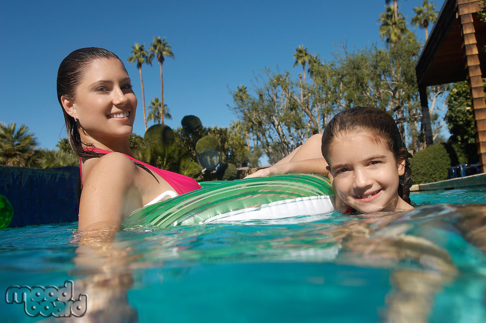 Mother and daughter floating on raft in swimming pool, portrait