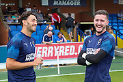 AFC Wimbledon goalkeeper Joe McDonnell (24) and AFC Wimbledon defender Will Nightingale (5) on the pitch prior to kick off smiling and laughing during the EFL Sky Bet League 1 match between AFC Wimbledon and Rotherham United at the Cherry Red Records Stadium, Kingston, England on 3 August 2019.