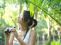 Young woman in tropical forest holding binoculars