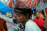 Hatian woman delivering wares in Santiago marketplace.