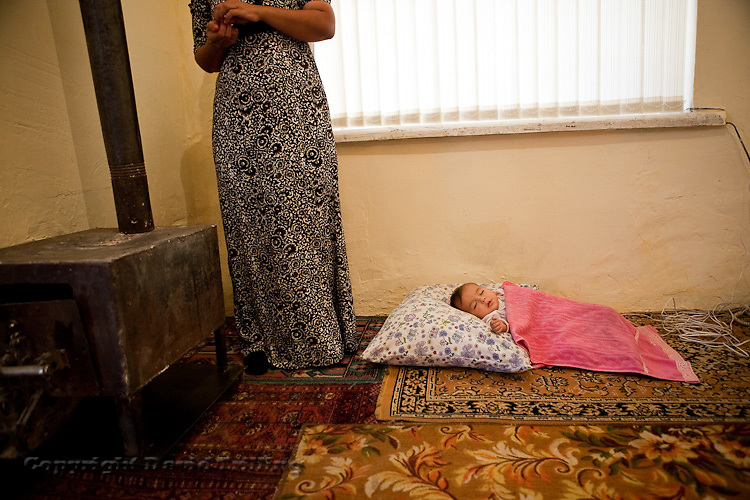 A woman watches over her baby as she visits relatives in Ashgabat for a holiday meal during Gurban Bayram, the Feast of the Sacrifice.