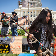 "Carrie Sage Curley, San Carlos Apache, dances to music played by fellow members of the San Carlos Apache Tribe and their supporters in front of the United States Capitol to protest the transfer of Apache land to a private Australian-British mining corporation.  In December 2014, a rider to the National Defense Authorization Act handed over Oak Flat to a foreign-owned company looking to mine copper.  The Apache are currently ""occupying"" Oak Flat, and travelled to D.C. to protest the action.  In response, Rep. Raul Grijalva (D-AZ-3), proposed the Save Oak Flat Act (H.R. 2811) in June, 2015 to repeal the land exchange.  John Boal Photography"