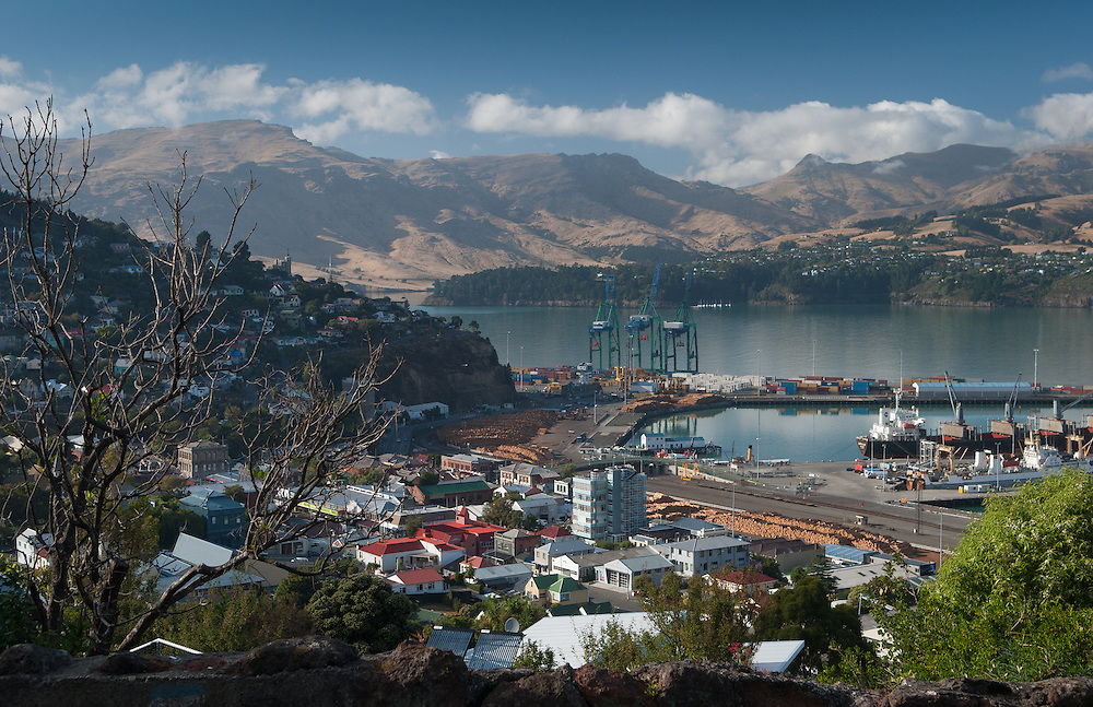 Elevated view of Lyttelton, Canterbury, New Zealand, looking out over the township, commercial port and distant mountain landscape, framed by trees