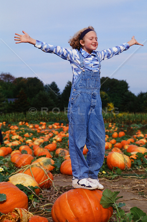 girl enjoying the feel of the air while standing on a large pumpkin in a pumpkin patch in Southampton, NY