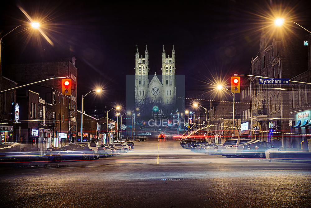 The Basilica of Our Lady is lit up against the night sky, seen at the end of MacDonell street downtown Guelph.  Photo by Andrew Goodwin