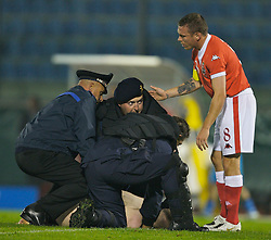 San Marino, San Marino - Wednesday, October 17, 2007: Wales' captain Craig Bellamy makes sure the San Marino riot police don't use too much force on a naked streaker who ran on to the pitch to entertain the fans during the Group D UEFA Euro 2008 Qualifying match at the Serravalle Stadium. (Photo by David Rawcliffe/Propaganda)