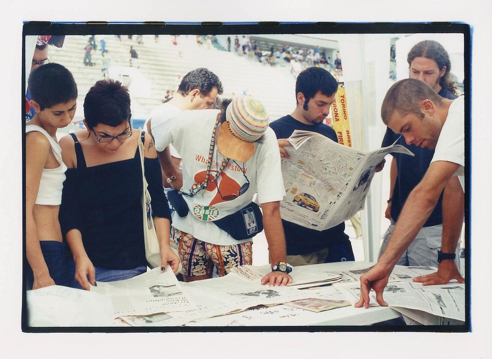 Proteste contro il summit del G8, Genova luglio 2001. 19 Luglio. Manifestanti leggono i giornali all'info point dello stadio Carlini.