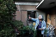 Kawasaki, November 21 2014 - Japanese artist Tatsumi ORIMOTO, 69, at home offering some rice to the nature.