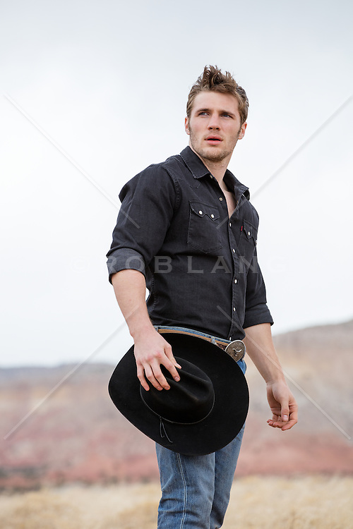 All American cowboy outdoors with a mountain view