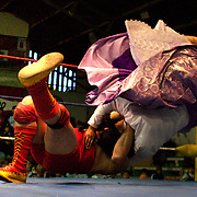 Cholita Yolanda La Amorosa is knocked unconscious from this throw while fighting with Barba Negra during the 'Titans of the Ring' wrestling group performance at El Alto's Multifunctional Centre. Bolivia. The wrestling group includes the fighting Cholitas, a group of Indigenous Female Lucha Libra wrestlers who fight the men as well as each other for just a few dollars appearance money. El Alto, Bolivia, 24th January 2010. Photo Tim Clayton