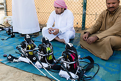 Man selling small robot jockeys at camel racing club at Al Marmoum outside Dubai  in United Arab Emirates