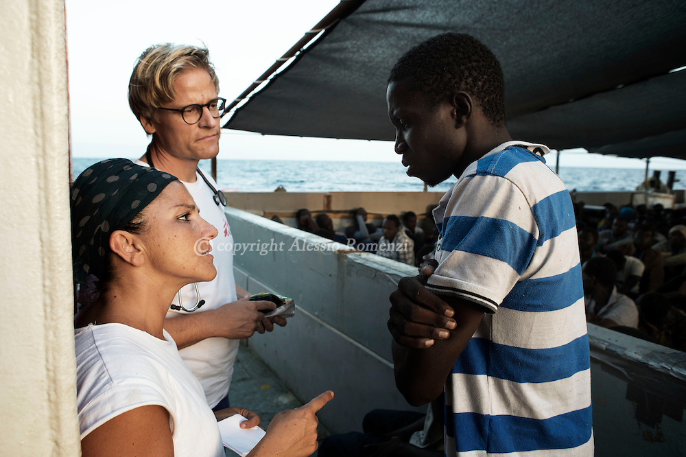 Italy: MSF Dignity1: MSF field coordinator Francesca Mancia (L) and doctor Tancred Stobe(C) interview an African migrant rescued at sea on the Dignity1 on August 23, 2015. Alessio Romenzi