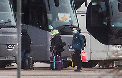 © Licensed to London News Pictures. 09/02/2020. Brize Norton, UK. Passengers board coaches after disembarking from a charter flight carrying Britons evacuated from Wuhan , China after it arrived at RAF Brize Norton in Oxfordshire. Fears of the spread of the corona virus have lead to this third charter flight being organised to bring 200 people to the UK. The passengers will be quarantined at a facility in Milton Keynes for 14 days. Photo credit: Peter Macdiarmid/LNP