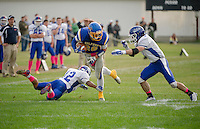 Gilford's Kyle Gaudet attempts to run through Interlakes Malik Carter and Nick Brothers during NHIAA Division III Football at the Meadows Field on Saturday afternoon.  (Karen Bobotas/for the Laconia Daily Sun)