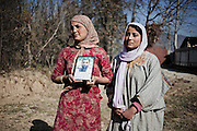 Talisma (28) and Kolsuma (21), holding the picture of their father disappeared  during the clashes in the 90', 14, November 2010,Zogyar village, Baramulla district, Kashimr.