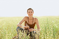 Young woman crouching in field of grass. portrait