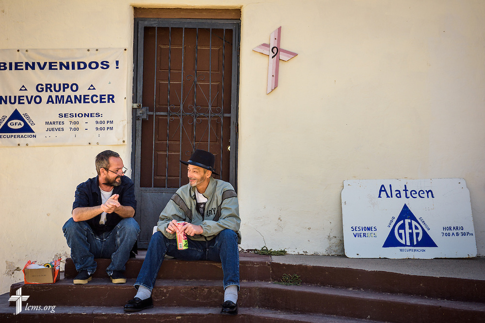 Blaine NiCastro and Michael LaBrecque chat on the steps outside the side door of San Pablo Lutheran Church on Saturday, May 21, 2016, at Ysleta Lutheran Mission Human Care in El Paso, Texas. The two were waiting for the weekly food distribution to begin. LCMS Communications/Erik M. Lunsford