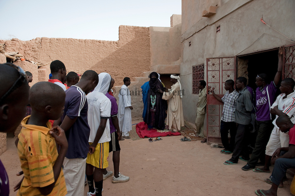"Mohamed aka ""Boss"" wearing the Tuareg traditionnal dress in the ghetto. Some young african migrants are watching him."