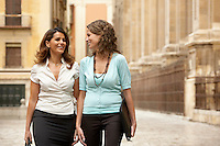 Two businesswomen walking through town together.