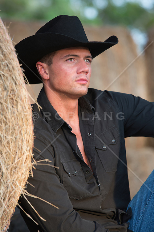 portrait of a handsome cowboy near hay bales