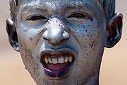 Indian boy celebrating annual Hindu Holi festival of colours smeared with powder paints in Mumbai, formerly Bombay, Maharashtra, India