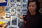 Panjiayuan weekend market. Fine art photographer selling black and white prints of Southern tribes people.