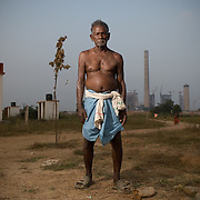 Bhoi Oram (80) and the chimneys of the industrial project towering over the resettlement colony at Jharsuguda, Orissa.