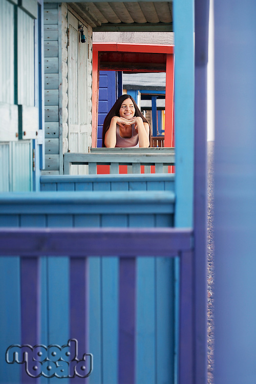 Woman leaning on balustrade of beach house