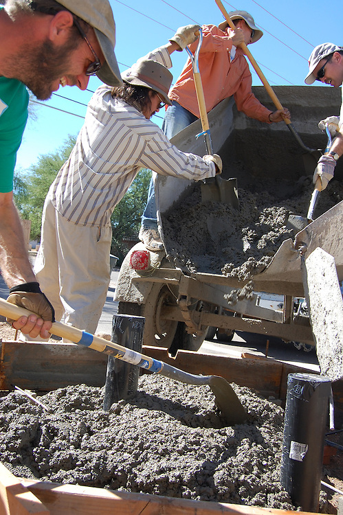 Watershed Management Group staff and volunteers guide the cement pour into the form for the cistern base.