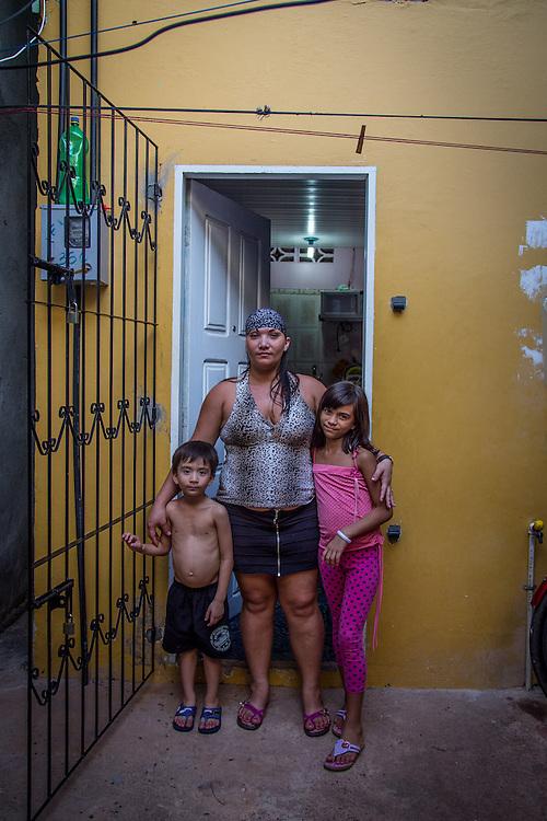 Yvonne, 29 anni, con i suoi due figli davanti a casa. Al posto della parrucca preferische una bandana. Molte delle vittime arrivano in città senza molte risorse e finiscono ad abitare in zone povere e disagiate.