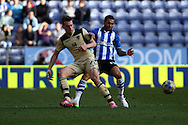 Charlie Taylor of Leeds United and Jermaine Pennant of Wigan Athletic (r) challenge for the ball. Skybet football league championship match , Wigan Athletic v Leeds Utd at the DW Stadium in Wigan, Lancs on Saturday 7th March 2014.<br /> pic by Chris Stading, Andrew Orchard sports photography.