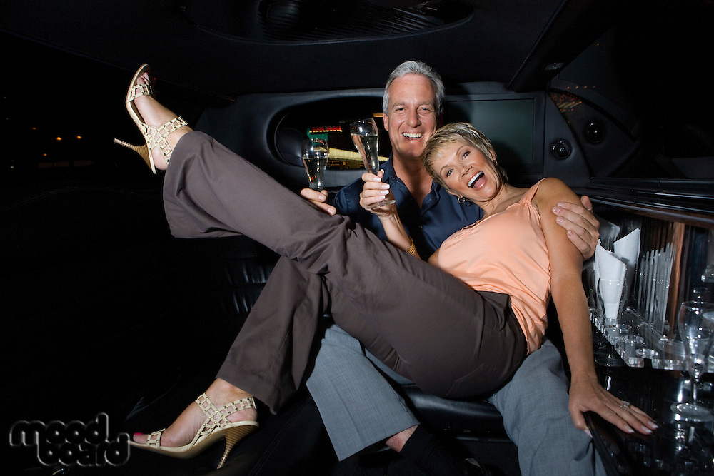Middle-aged couple sitting on back seat of limousine