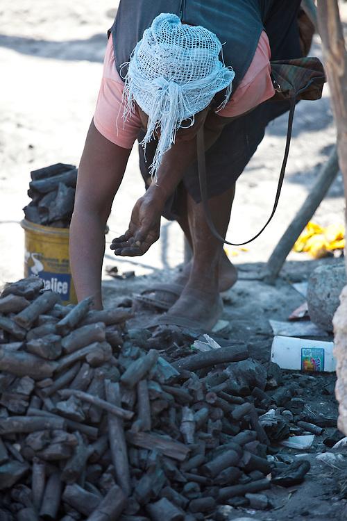 A woman sells charcoal at a market in Anse a Galet, Ile de la Gonave, Haiti