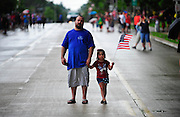 Terry Madison, of Burbank, and his daughter Emma, 5, watch as the Mokena Fire Department raise an American flag in honor of PFC Aaron Toppen before his casket arrives for a funeral service. Saturday, June 21st, 2014, in Mokena.