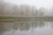 Morning fog partially obscures the autumn trees and their reflections on Kendall Lake, located in the Cuyahoga Valley National Park, Ohio.