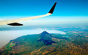Wing of an airplane frames the very active Momotombo Volcano and Lake Managua in Nicaragua.