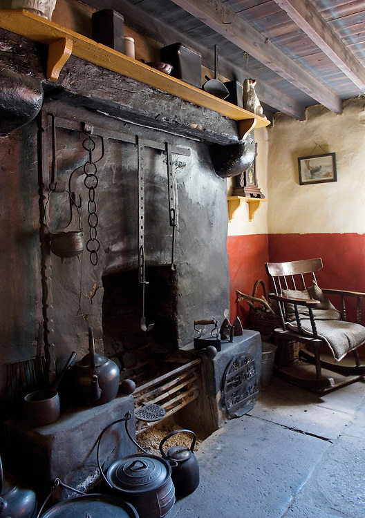 Ulster Folk and Transport Museum, Cultra, Belfast. 19th C. Coshkib Hill Farm. Fireside with cranes, hobs, rocking chair.