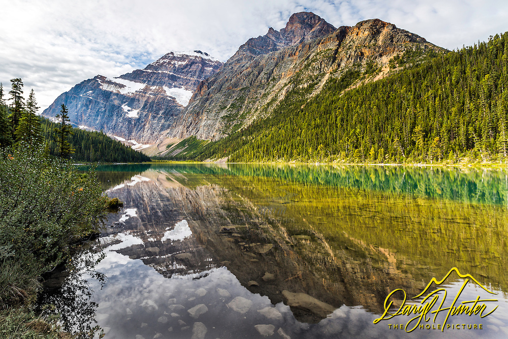 The towering heights of Mount Edith Cavell reflection upon the still water of Lake Cavell in Jasper National Park